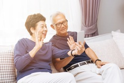 Senior couple grand parents making a video call and waving at the caller