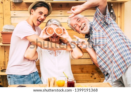 Senior couple grandparents with teenager nephew having fun at breakfast. Craziness and laughs. Wood on background and on table.Three people enjoying life. Food and drink