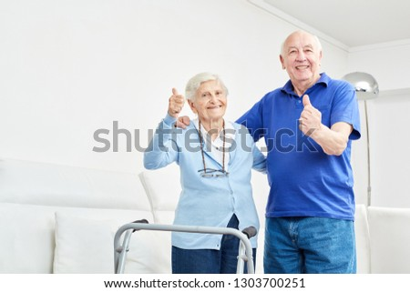 Senior couple happily holding their thumbs up as a sign of success and confidence