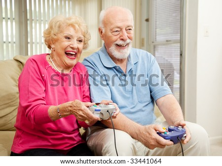 Senior couple has fun at home playing video games together.