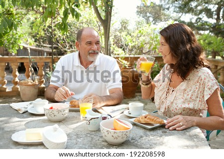 Senior couple having breakfast together at a table in a luxury hotel garden during a sunny day. Mature people eating healthy food and having a conversation. Outdoors lifestyle.