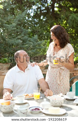 Senior couple having breakfast together at a table in a luxury hotel garden during a sunny day. Mature people eating healthy food drinking coffee and juice in each others company. Outdoors lifestyle.