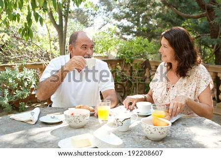 Senior couple having breakfast together sitting at a table in a luxury hotel garden on holiday. Mature joyful people eating healthy food, having a conversation drinking coffee. Outdoors lifestyle.