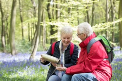 Senior Couple Having Drink From Flask On Walk Through Bluebell Wood