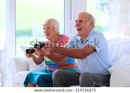 Senior couple having fun at home playing video game holding joysticks in hands sitting cozy on the sofa in bright sunny living room with big windows. Happy retirement concept.