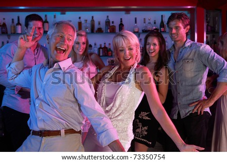 Senior Couple Having Fun In Busy Bar