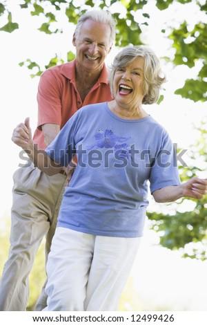 Senior couple having fun outside in park - stock photo