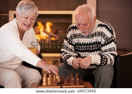 Senior couple having fun with chess at home on winter night woman moving chess man on board, man looking surprised.