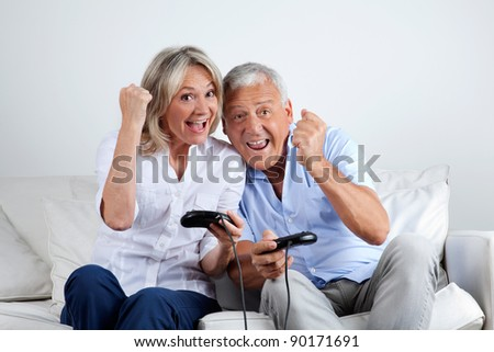 Senior couple having great time playing video game together