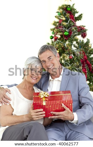 Senior couple holding a Christmas present at home