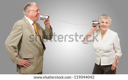 Senior Couple Holding A Tin On Gray Background