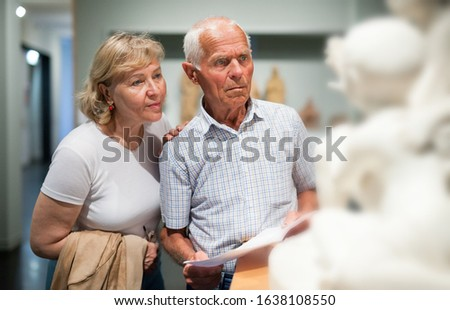 Senior couple holding brochure with information about exhibits on exposition of museum