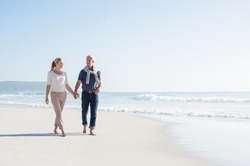 Senior couple holding hands at the beach on a sunny day. Mature couple in love holding hands and looking each other at the seaside. Smiling wife and happy husband walking barefoot on the white sand.