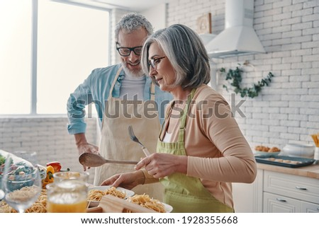 Senior couple in aprons preparing healthy dinner and smiling while spending time at home Сток-фото ©