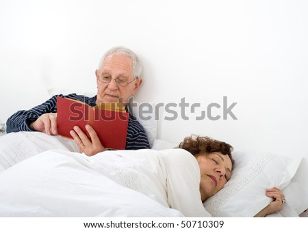 senior couple in bed man reading and woman is asleep