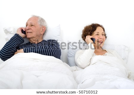 senior couple in bed talking on the phone