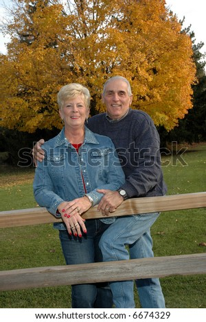 senior couple in front of an autumn tree