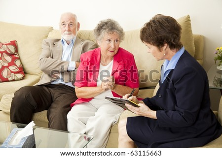 Senior couple in marriage counseling.  The wife talks while the counselor takes notes. - stock photo