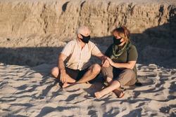 Senior couple in the beach wearing medical mask to protect from coronavirus in summer day, coronavirus quarantine
