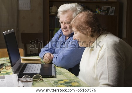 Senior Couple in their Dining Room with a Laptop Computer