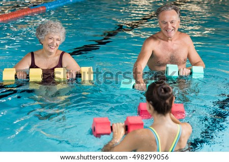 Senior couple in training session of aqua aerobics using dumbbells in swimming pool. Mature man and old woman practicing aqua fitness together. Healthy and fit senior couple doing aqua aerobics.