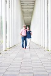 Senior Couple In White Pillar Hallway