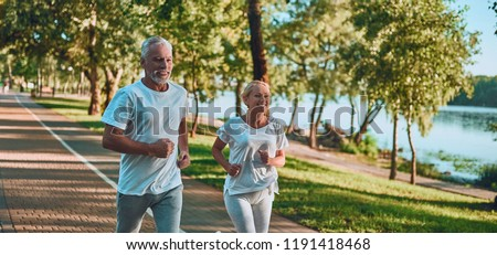 Senior couple is doing sport outdoors. Running in park in the morning. stock photo