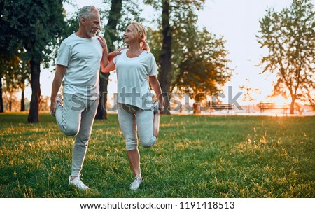 Senior couple is doing sport outdoors. Stretching in park during sunrise. stock photo