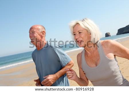 Senior couple jogging on a sandy beach - stock photo