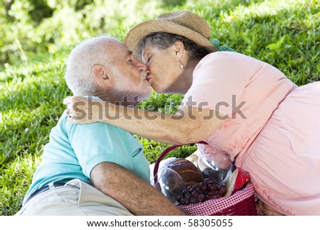 Senior couple kissing on a romantic picnic in the park.