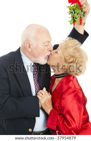 Senior couple kissing under the Christmas mistletoe. White background ...
