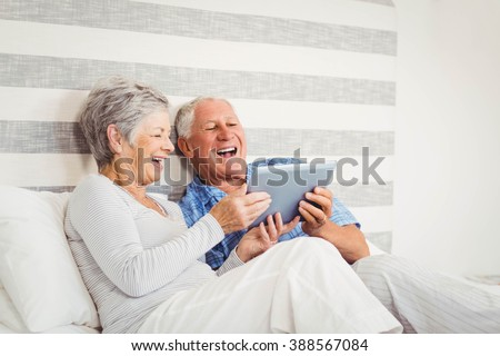 Senior couple laughing while using digital tablet in bedroom
