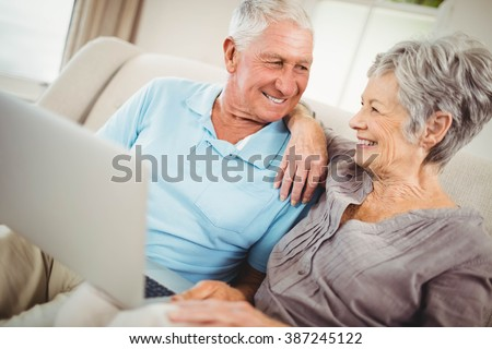 Senior couple looking at each other and smiling in living room #387245122