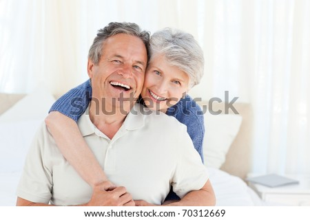 Senior couple looking at the camera  at home