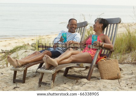 Senior couple lounging on beach with drinks