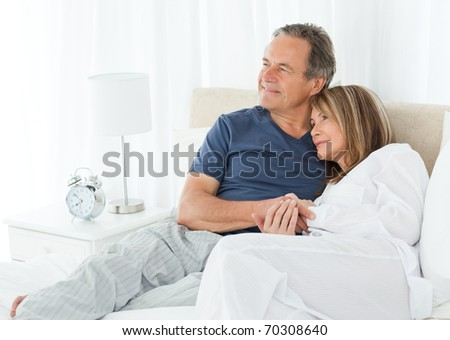 Senior couple lying down on their bed at home