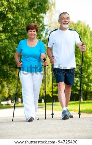 senior couple making nordic walking in the park - stock photo