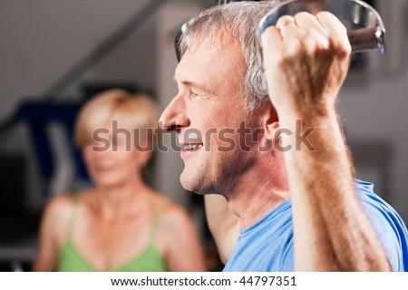 Senior couple -  man and woman - in the gym lifting weights on a lat pull machine, exercising