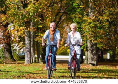 Senior couple, man and woman, on bicycles having bike tour in autumn park #474835870