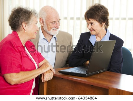 Senior couple meet with a sales woman or financial consultant.