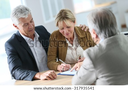 Senior couple meeting real-estate agent for investment - Shutterstock ID 317935541