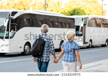 Senior couple of tourists on vacation in front of tourist bus