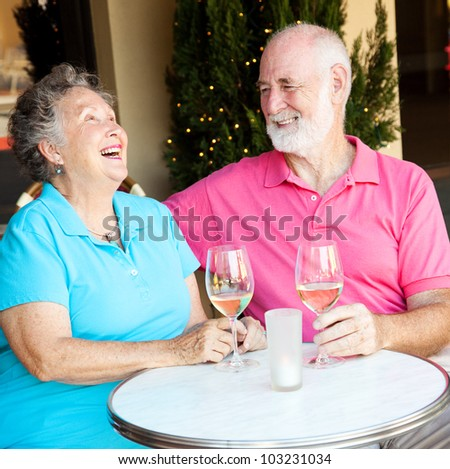 Senior couple on a date, laughing together over wine.