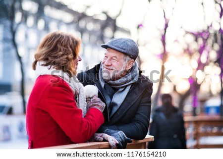 Senior couple on a walk in a city in winter.