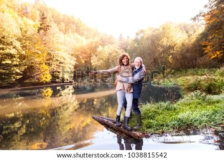 Senior couple on a walk in autumn nature.