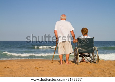 senior couple on beach, the wife is disabled and sitting on wheelchair