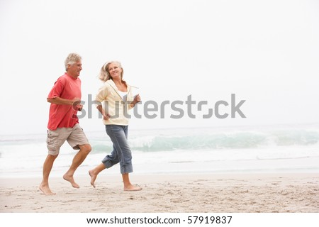 Senior Couple On Holiday Running Along Winter Beach