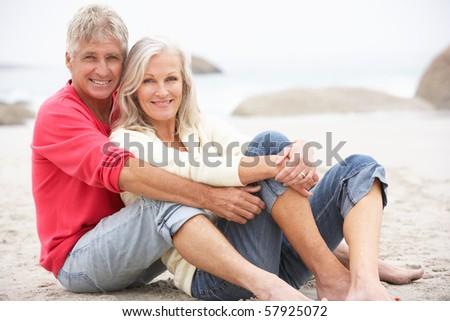 Senior Couple On Holiday Sitting On Winter Beach - stock photo