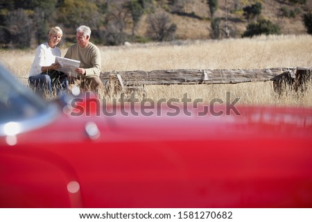 Senior couple on road trip check map in countryside classic car