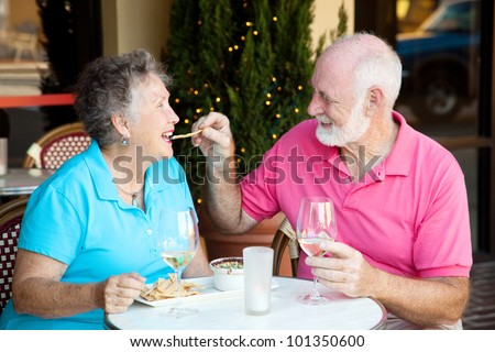 Senior couple on romantic lunch or dinner date.  He's feeding her the appetizer by hand.